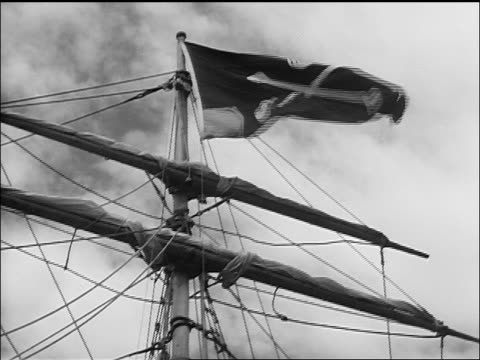 low angle close up skull + crossbones on flag on ship's mast / treasure island (1934) - seeräuber stock-videos und b-roll-filmmaterial