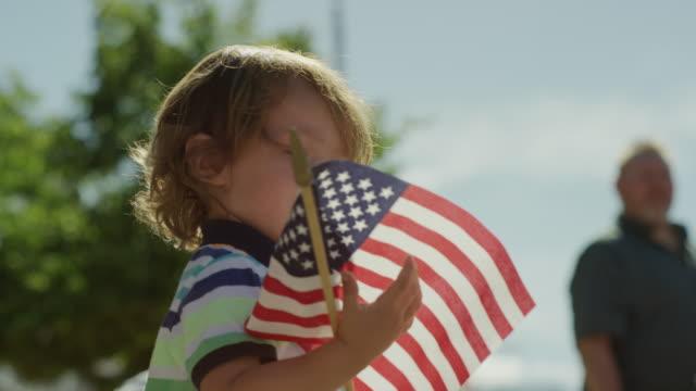 Low angle close up slow motion shot of boy waving American flag at parade / American Fork, Utah, United States
