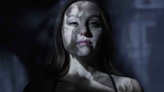 vídeos y material grabado en eventos de stock de low angle close up slow motion shot of projections on face of woman / cedar hills, utah, united states - futurista