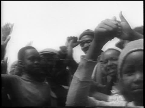 B/W 1961 low angle close up smiling Black people in protest against apartheid laws / South Africa / newsreel