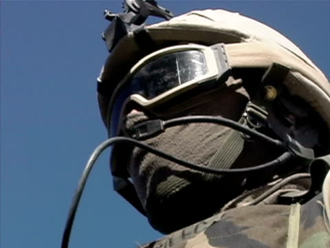 low angle close up soldier adjusting microphone near mouth/ afghanistan - operazione enduring freedom video stock e b–roll