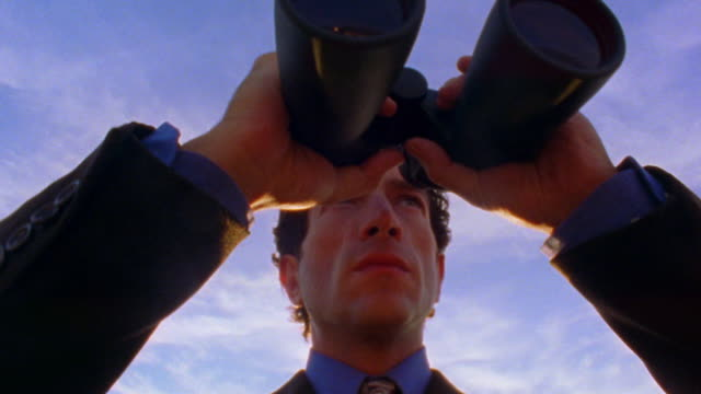 low angle close up tilt up man in suit lifting binoculars to eyes outdoors - curiosity stock videos & royalty-free footage