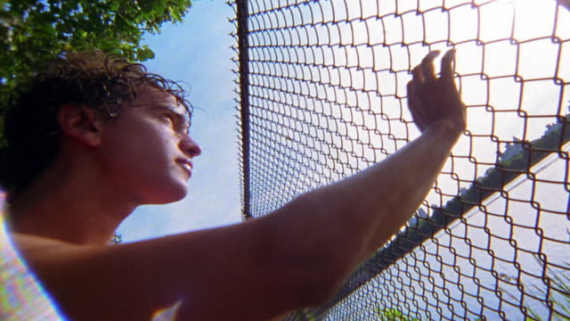 low angle close up tilt up shirtless man stretching against chain link fence and drinking water / central park, nyc - shirtless stock videos & royalty-free footage