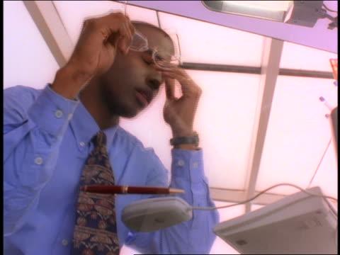 vídeos de stock, filmes e b-roll de low angle close up tired black businessman sitting at desk rubbing head with hands - vestuário de trabalho formal