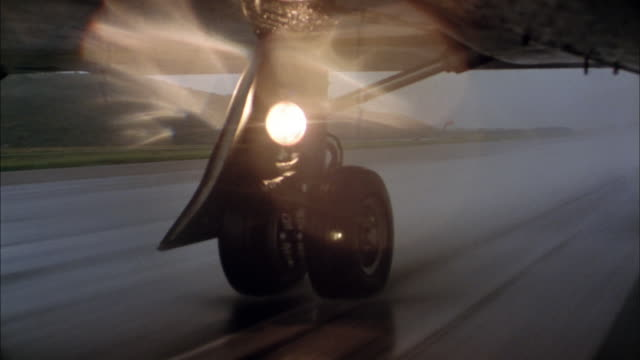 low angle close up tires of jet preparing for take off on runway w/light reflecting on cam - viewpoint stock videos & royalty-free footage