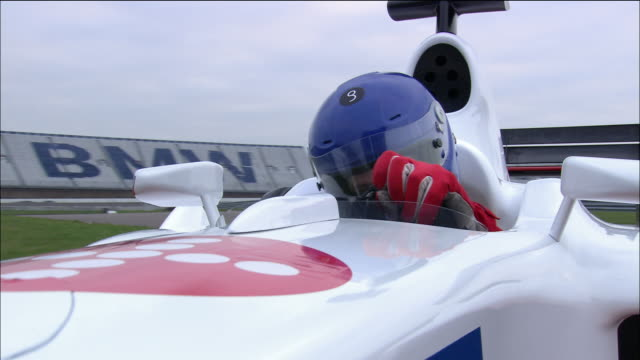 low angle close up tracking shot driver steering around curves in cockpit of formula one race car - lenkrad stock-videos und b-roll-filmmaterial