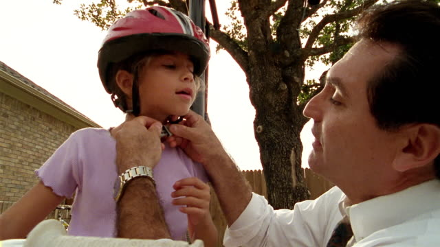 Low angle close up tracking shot father putting helmet on daughter / helping her ride bicycle
