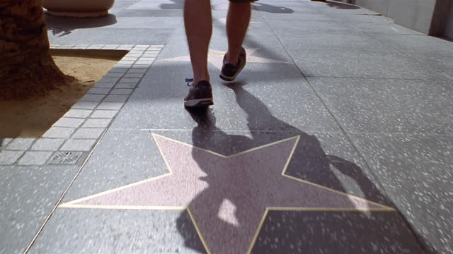 low angle close up tracking shot man's feet walking over stars on hollywood walk of fame - ウォークオブフェーム点の映像素材/bロール