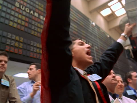 low angle close up pan trader shaking arms + shouting beneath display board / commodity exchange, nyc - bull market stock videos & royalty-free footage