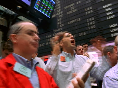 low angle close up pan traders shaking arms + shouting beneath display board / commodity exchange, nyc - bull market stock videos & royalty-free footage