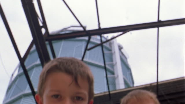 Low angle close up two young boys looking down into CAM w/glass roof in background