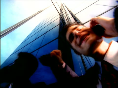 OVEREXPOSED low angle close up upset businessman talking, shaking head + pounding fist on mirrored building