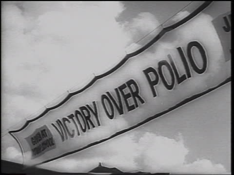 b/w 1962 low angle close up victory over polio banner with clouds in sky in background / texas / newsreel - polio stock videos & royalty-free footage