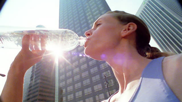 Low angle close up woman drinking from water bottle with office buildings in background / Los Angeles