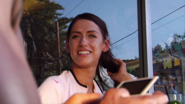 stockvideo's en b-roll-footage met low angle close up woman smiling / tilt down to man text messaging with smart phone - elektronische organiser