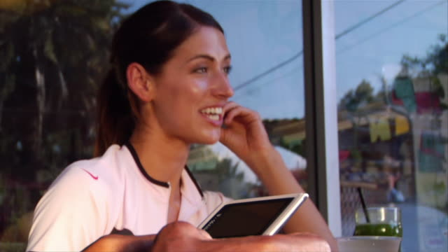 low angle close up woman talking and smiling as man text messages with smart phone in foreground - meno di 10 secondi video stock e b–roll