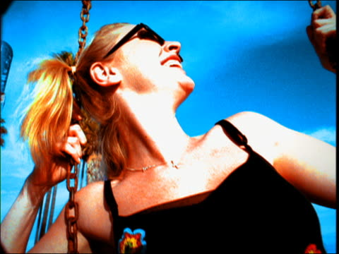 Low angle close up young blonde woman laughing and sitting on swing outdoors / Los Angeles