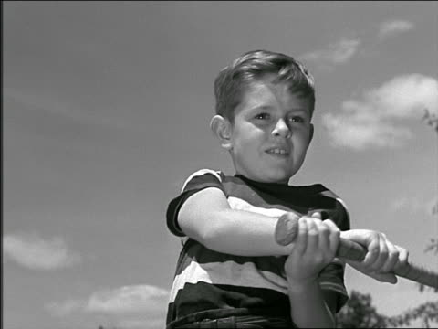 b/w 1948/49 low angle close up young boy swinging baseball bat outdoors - baseball bat stock videos & royalty-free footage