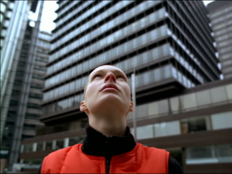 vidéos et rushes de low angle close up young woman with shaved head looking up / skyscrapers in background / london - en l'air