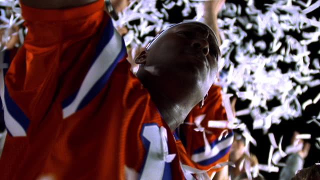 low angle MS close up zoom in Black man cheering + clapping in bleachers of football stadium with confetti falling