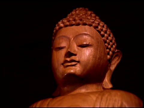 low angle close-up of a wooden buddhist statue in a temple. - weibliche figur stock-videos und b-roll-filmmaterial