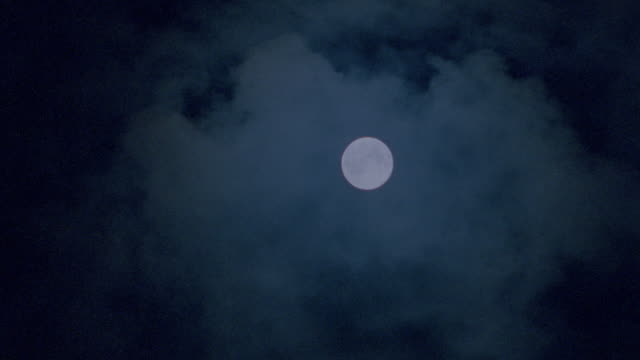 low angle clouds passing in front of full moon