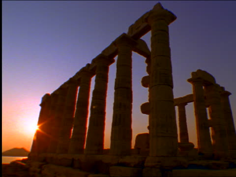 low angle columns of temple of poseidon at sunset / aegean sea in background / cape sounion, greece - sounion stock videos and b-roll footage