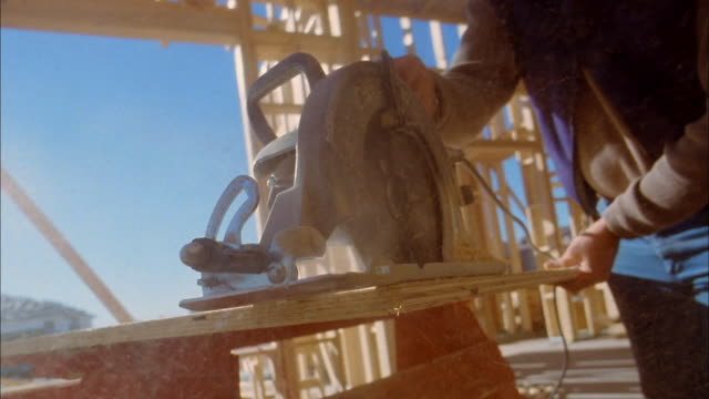 stockvideo's en b-roll-footage met low angle construction worker cutting board w/circular saw / phoenix, arizona - bouwapparatuur