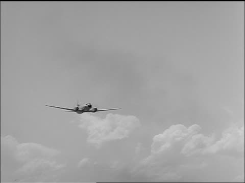 b/w 1957 low angle pan continental twin-prop airliner flies by low overhead - 1957 stock videos & royalty-free footage