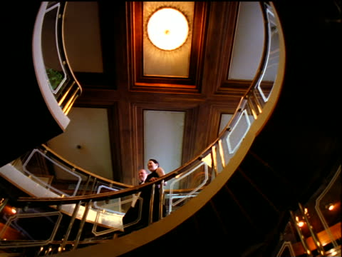 low angle PAN couple in formalwear walking down spiral staircase in cruise ship / Egypt