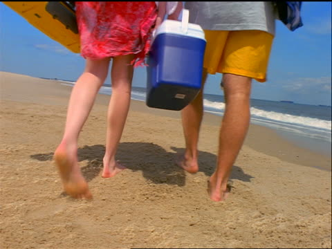 rear view low angle couple in hats carrying beach gear + walking on beach away from camera - cool box stock videos & royalty-free footage