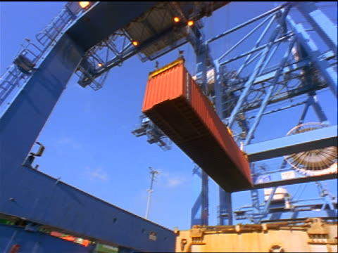 low angle crane picking up red shipping container + loading it onto ship / port of tacoma, washington - crane stock videos & royalty-free footage