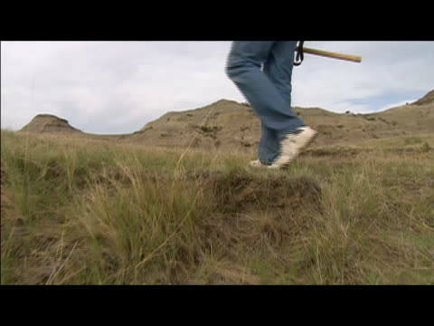 low angle crane shot following behind legs of archeologist walking up hill with pick / crane past man to view of hell creek formation / montana - crane shot stock videos & royalty-free footage