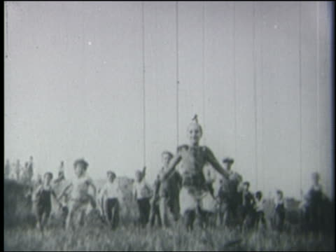b/w 1928 low angle crowd of children running down hill toward + past camera - 1928 stock videos & royalty-free footage