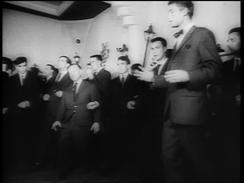 B/W 1961 low angle crowd of men dancing the Twist on dance floor / newsreel