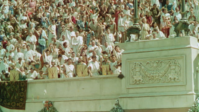 vídeos de stock, filmes e b-roll de low angle pan crowd of romans cheering + throwing things in arena in ancient rome / quo vadis (1951) - reconstituição histórica