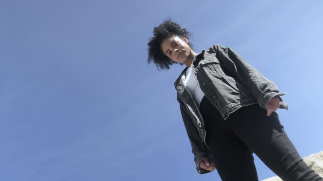 low angle, curly haired woman against blue sky - jeans bildbanksvideor och videomaterial från bakom kulisserna