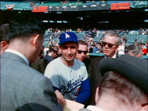 1965 low angle Dodger Sandy Koufax talking with reporters on field / industrial