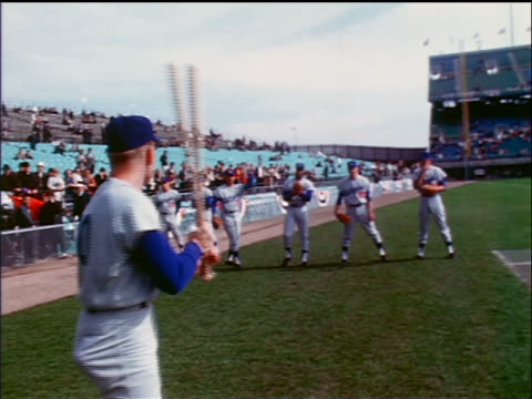 1965 low angle Dodgers batter pitchers warming up on sidelines / industrial