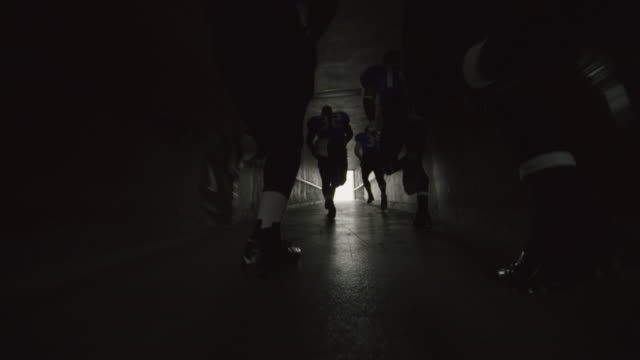 ws slo mo. low angle dolly shot as professional football players run through stadium tunnel on game day. - sportsperson stock videos & royalty-free footage
