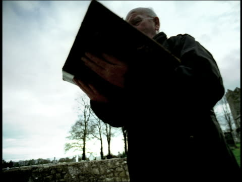 low angle dolly shot away from senior man in black reading aloud from large book in middle of cemetery / ireland - 薄毛点の映像素材/bロール