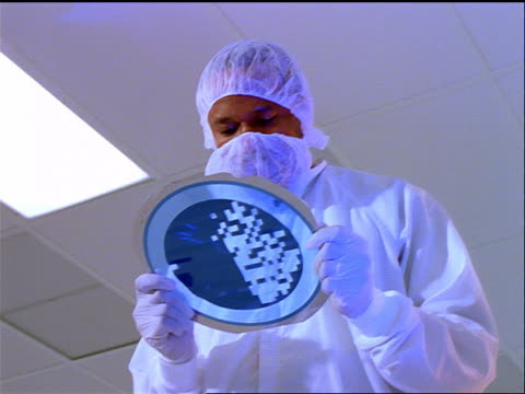 low angle dolly shot black male technician in protective clothing holding computer chip wafer in clean room - wafer stock videos and b-roll footage