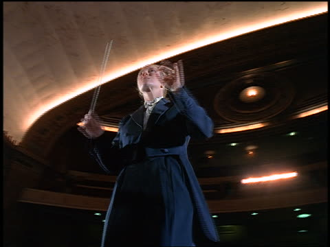 low angle dolly shot female conductor conducting in empty concert hall - conductor stock videos & royalty-free footage