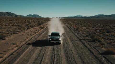 vídeos y material grabado en eventos de stock de low angle dolly shot filmed by drone showing a truck driving along a dry dirt road in a remote landscape, nevada, united states of america - carretera de tierra