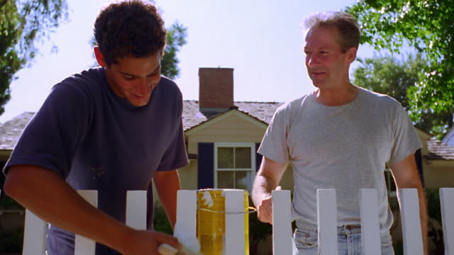 low angle dolly shot grey haired man + teenage boy painting white fence with house in background