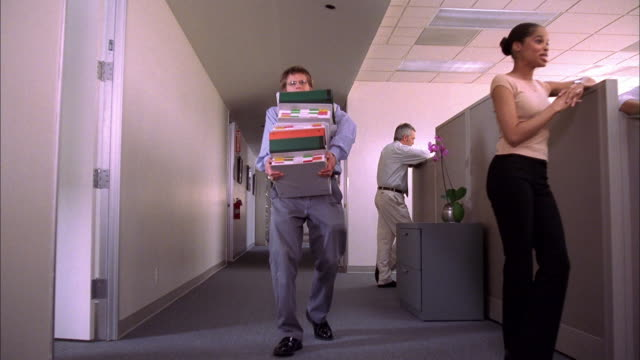 Low angle dolly shot man carrying overloaded stack of binders walking down office aisle