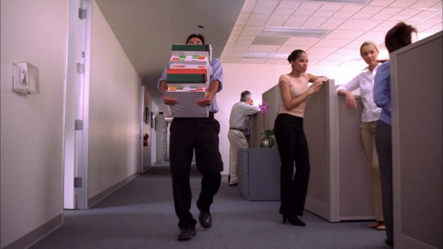 low angle dolly shot man carrying overloaded stack of binders walking down office aisle - 真剣点の映像素材/bロール