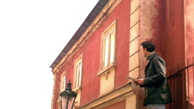vídeos y material grabado en eventos de stock de low angle ms dolly shot man standing next to building reading map + looking around / prague, czech republic - imagen virada
