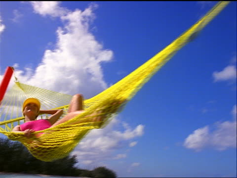 low angle dolly shot past woman in pink swimsuit + yellow visor lying in large yellow hammock / bahamas - swimming costume stock videos & royalty-free footage