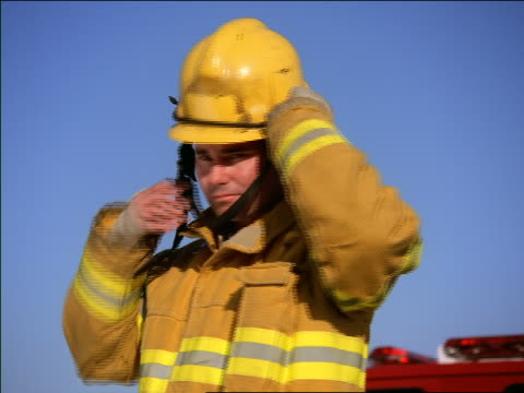 low angle MS dolly shot PORTRAIT firefighter putting on helmet + pulling strap tight